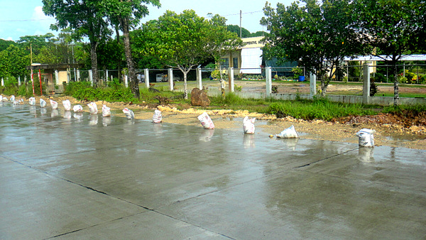 empty cement bags serve as border for new road