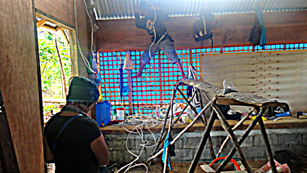 Joery balancing on the scaffold, installing wiring in the nipa hut
