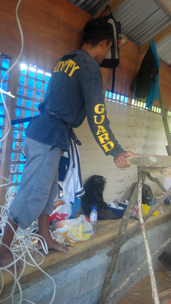 Joery installing wiring at the nipa hut