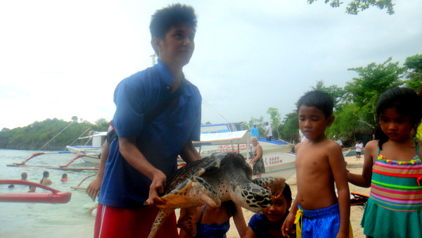 Mike lifts up the sea turtle