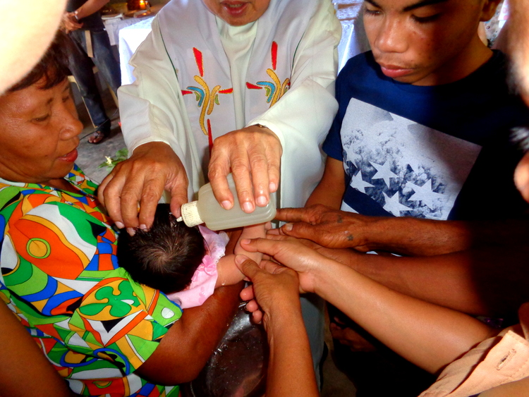 priest in philippines blesses child in christening